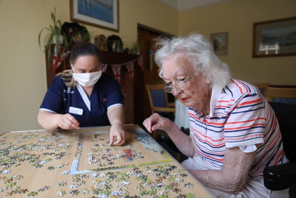 Nurse Ana and resident Enid make a puzzle together at Brendon Care, Winchester on June 23, 2020.  Photo credit should read: Isabel Infantes